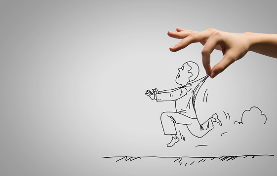 Close up of human hand catching running away businessman